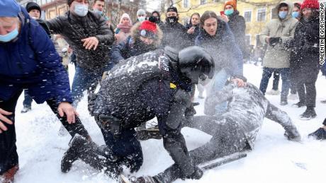 Un polițist arestează un bărbat în timp ce protestatarii încearcă să-l ajute, în timpul unui protest desfășurat duminică la Sankt Petersburg împotriva arestării liderului opoziției Alexei Navalny.