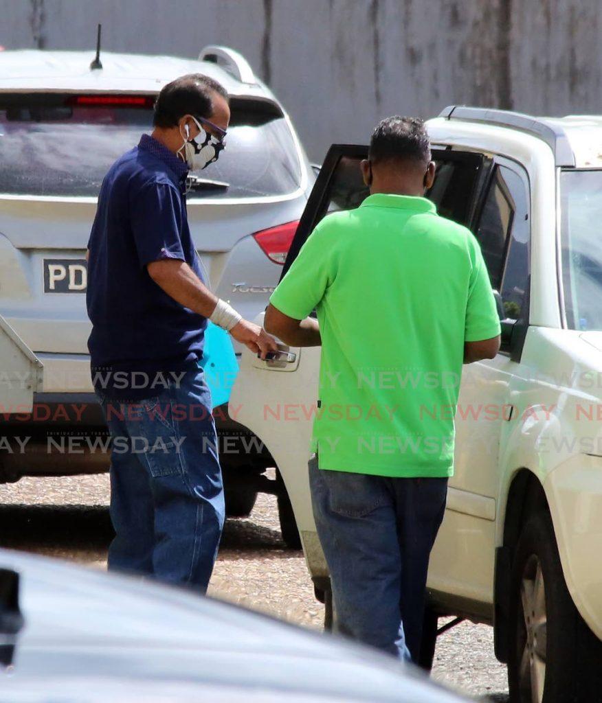 Randolph Bharat, tatăl lui Andrea Bharat (stânga), părăsește luni intrarea din spate a Centrului de știință criminalistică de pe drumul Barbados, Port of Spain.  - Surach Sholay