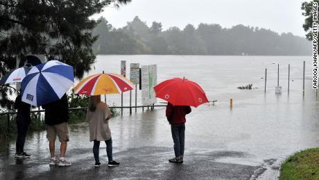 Locuitorii se uită la râul Nepean umflat în timpul ploilor abundente din vestul orașului Sydney pe 20 martie.