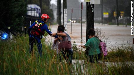 Un lucrător de salvare îi ajută pe rezidenți să traverseze un drum inundat din vestul orașului Sydney pe 20 martie