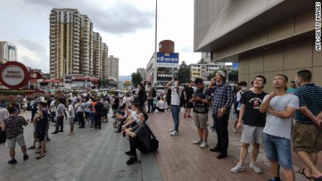 Cumpărătorii se uită la SEG Plaza din Shenzhen după ce au fost evacuați din clădirea vacilantă.