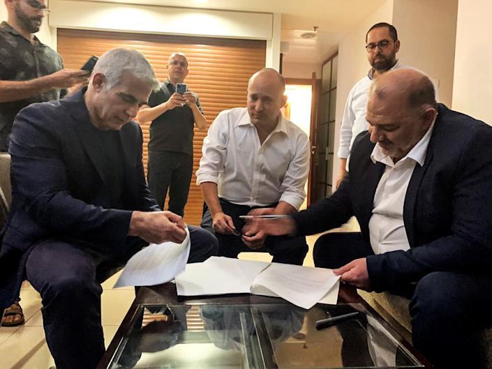 Liderul partidului Listă Arabă Unită Mansour Abbas, liderul partidului Yamina Naftali Bennett și liderul partidului Yesh Atid Yair Lapid, stau împreună la Ramat Gan, lângă Tel Aviv, Israel, 2 iunie 2021 (Ram / Post via Reuters)