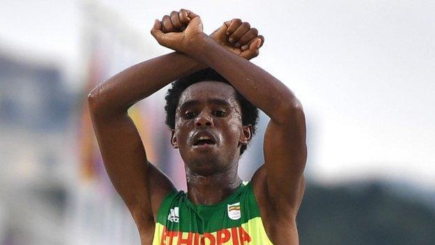 Feisa Lilisa, Etiopia, își încrucișează brațele deasupra capului la linia de sosire a cursului de atletism maraton masculin la Jocurile Olimpice Rio 2016 la Sampodromo din Rio de Janeiro pe 21 august 2016.