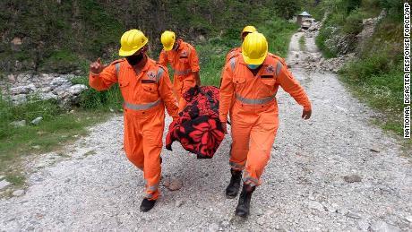 Soldații transportă cadavrul unei victime de pe locul unei alunecări de teren în Himachal Pradesh, India, pe 11 august.