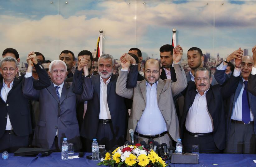 Înaltul oficial al Fatah, Azzam al-Ahmad (al doilea din stânga), prim-ministrul Hamas, Ismail Haniyeh (al treilea din stânga), și liderul Hamas, Musa Abu Marzouk (al patrulea din stânga), se țin de mână după ce acordul de reconciliere a fost anunțat în orașul Gaza, pe 23 aprilie, 2014. Hamas islamist cu sediul în Gaza și președintele Mahmoud A. (Sursa: Suhaib Salem / Reuters).