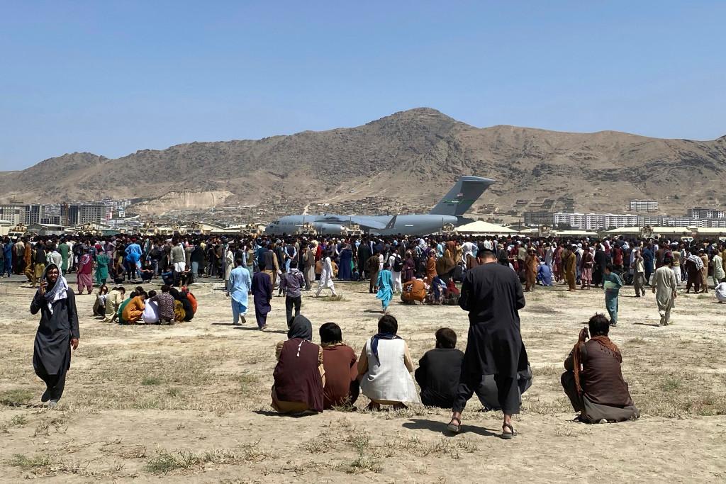 Sute de oameni se adună lângă un avion de transport C-17 al Forțelor Aeriene ale SUA.