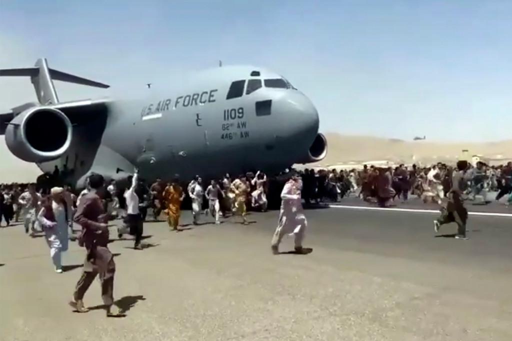 Sute de oameni aleargă alături de un avion de transport C-17 al Forțelor Aeriene ale SUA în Afganistan.