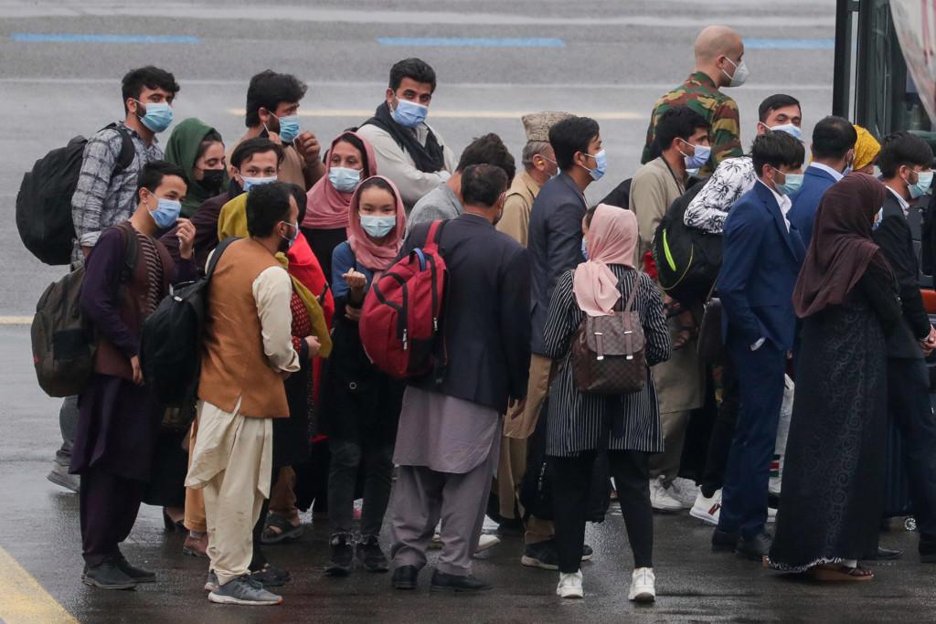 Oamenii se aliniază pentru a urca într-un autobuz după ce au debarcat un avion de evacuare Air Belgium din Afganistan pe aeroportul militar Millsbrook, pe 23 august 2021.