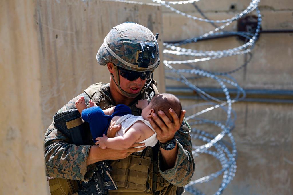 Un marine americane escortează un sugar în timp ce așteaptă mama în timpul unei operațiuni de evacuare pe Aeroportul Internațional Hamid Karzai, din Kabul, Afganistan.