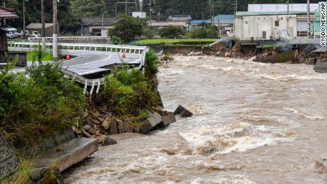 Un drum deteriorat de râul Suzuhari umflat din cauza ploilor abundente din Hiroshima, Japonia, pe 13 august.